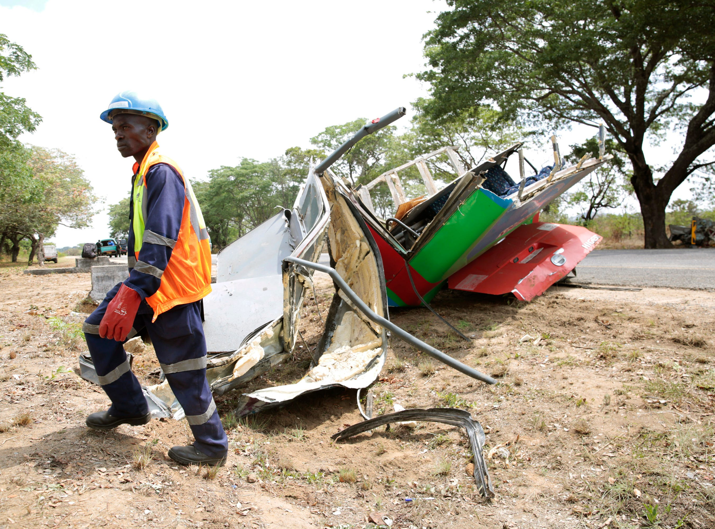A rescue worker at the scene of a bus crash in Rusape, Zimbabwe, Thursday, Nov. 8, 2018. A head-on collision between two buses has killed 47 people, where road accidents are common due to poor roads and bad driving.