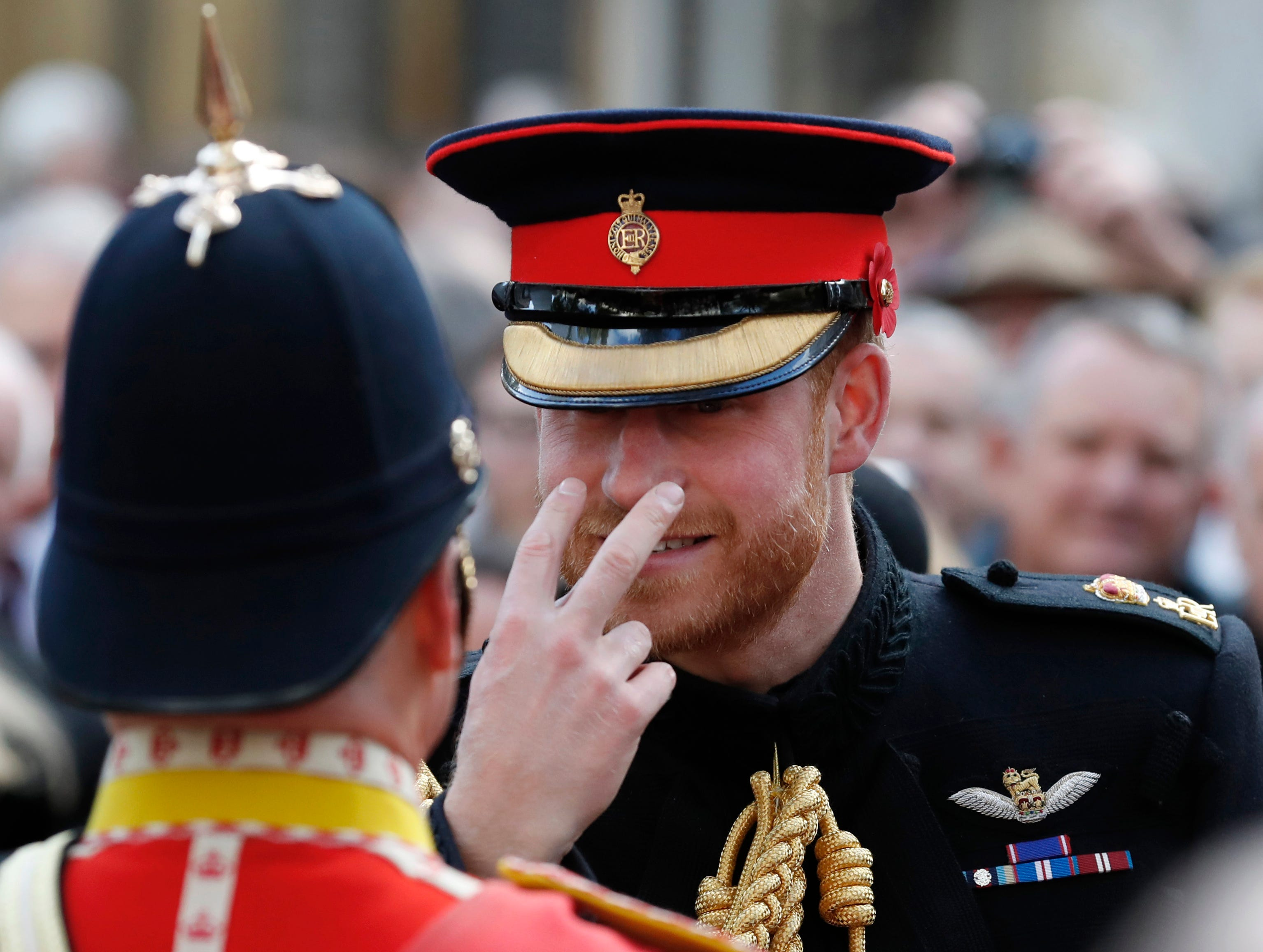 Britain's Prince Harry gestures to a serviceman as he attends the annual Field of Remembrance service at Westminster Abbey in London, Thursday, Nov. 8, 2018. The centenary of the end of hostilities in World War I will be marked with large commemoration services in London, Paris and on the battlefields of northern France, on Sunday, Nov. 11.