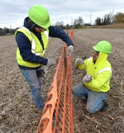 James Goulais, left, of Algonac, and Ken Tomchek, right, of Warren, use zip ties to attach sections of snow fence to fence posts on Nov. 7, 2018