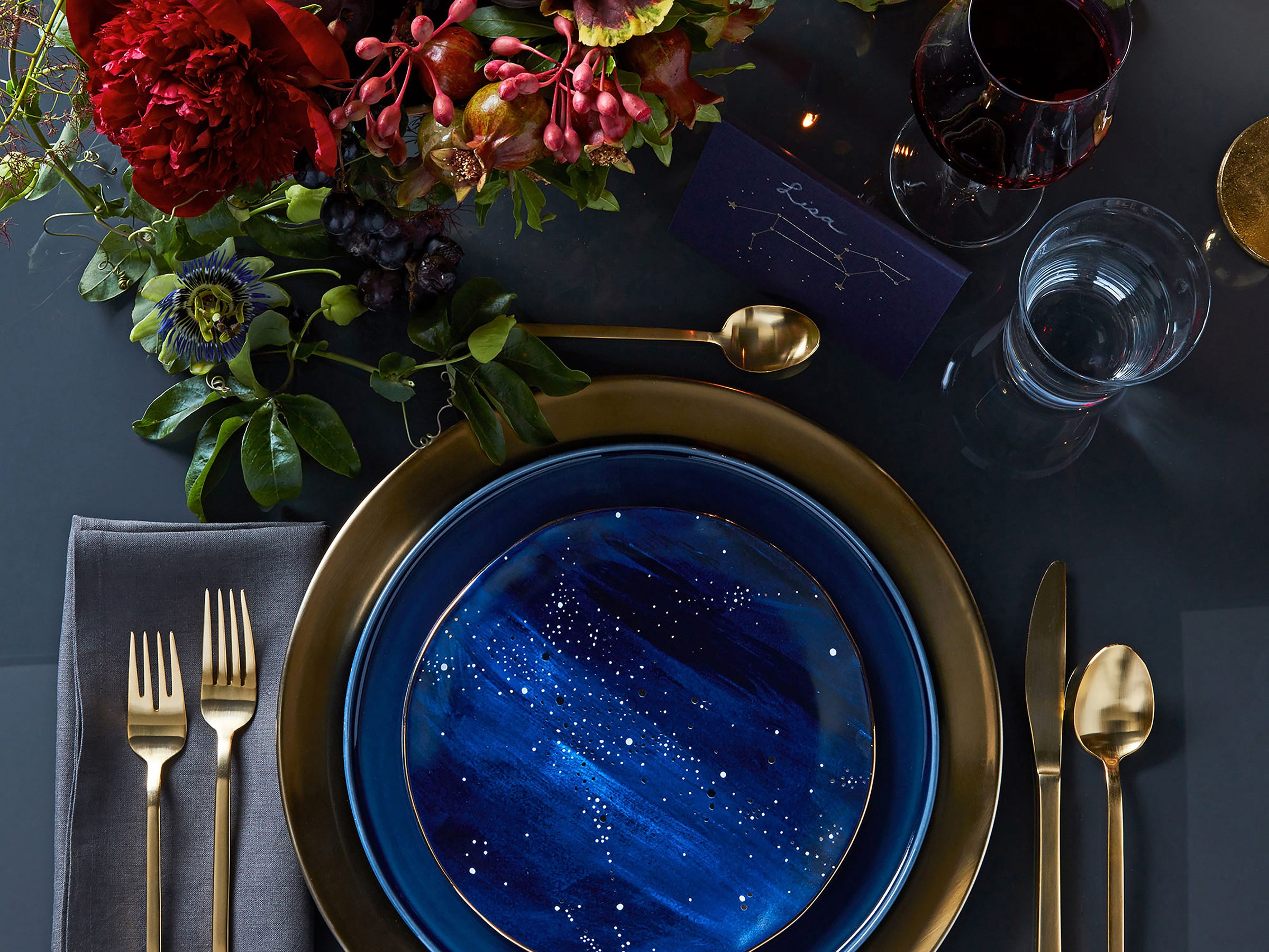The sky's the limit with possibilities for the Constellation salad plate from West Elm. Here, the hand-glazed stoneware is shown in a moody, deep blue ground with gold celestial sprays. There's also gold flatware, with strategic touches of gold and yellow in the flowers.