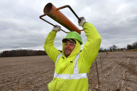 Ken Tomchek, of Warren, carries a 35-pound fence-post driver over his head as he walks between fence posts that he pounds into the ground.