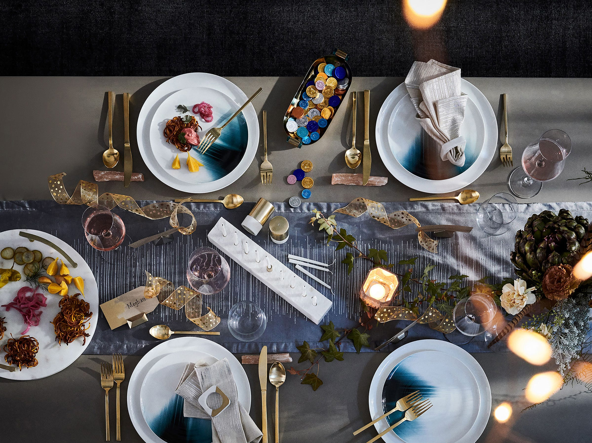 A fresh take on the Hanukkah table shows artistic plates with asymmetrical patterns that look like they were just painted, from West Elm. Even the traditional coins (usually wrapped in gold and silver) show up in unexpected foil wraps. And the 13-inch-long menorah itself has a modern look. A lustrous pewter velvet runner printed with metallic lines adds a luxe note.