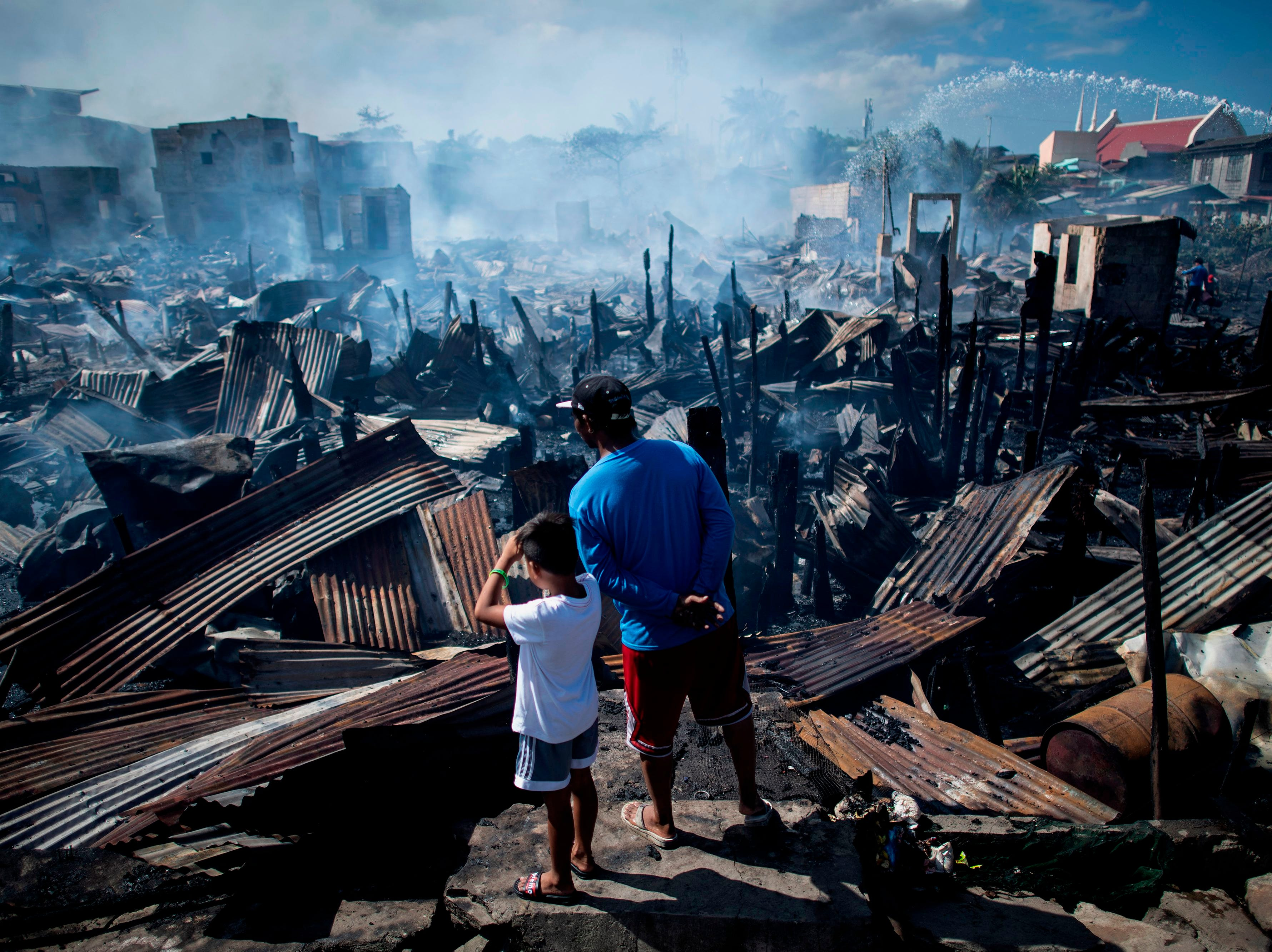 Residents stand amid houses destroyed by a fire in Navotas, Philippines, Nov. 8, 2018. Some 150 families were affected by the fire, according to local media reports.