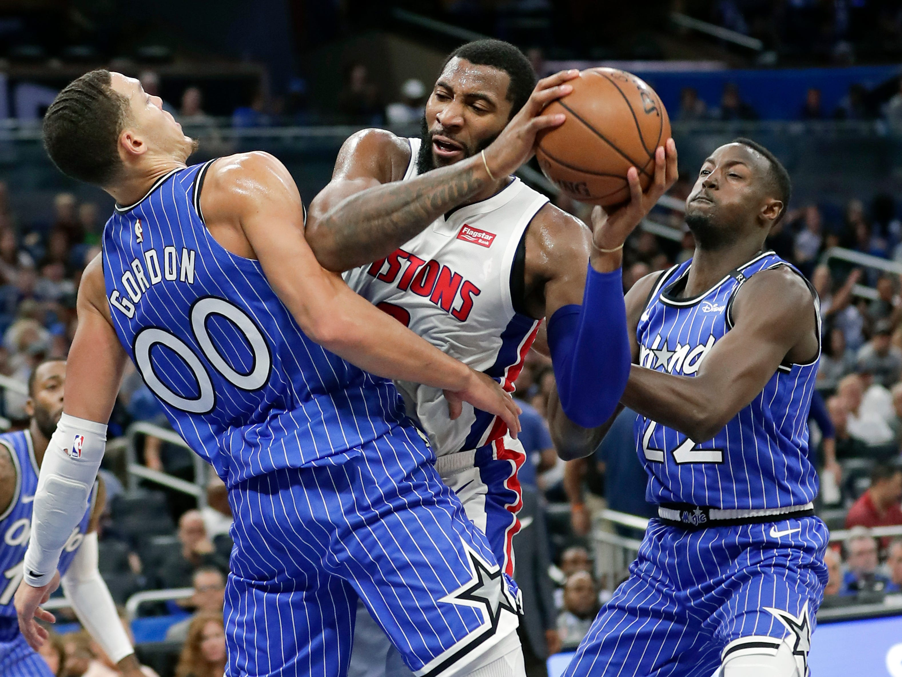 Detroit Pistons' Andre Drummond, center, tries to get to the basket between Orlando Magic's Aaron Gordon (00) and Jerian Grant, right, during the first half of an NBA basketball game, Wednesday, Nov. 7, 2018, in Orlando, Fla.