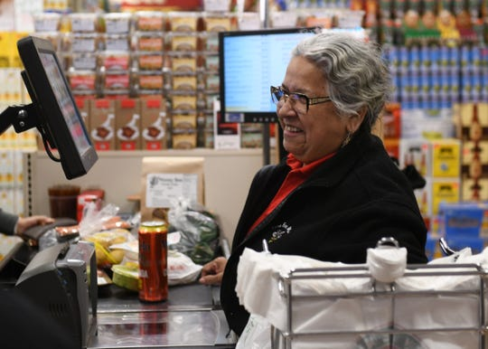 Cashier Phyllis Zuniga of Detroit wrings up a customer's purchase at Honey Bee Market in Detroit Thursday. Zuniga lives not too far from work. The manager says they are hiring for the holiday season.