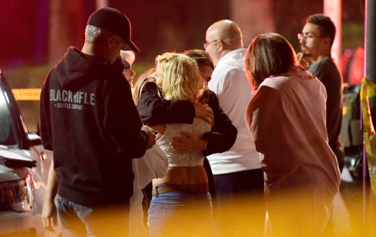 """People comfort each other as they stand near the scene Thursday in Thousand Oaks, Calif., where a gunman opened fire Wednesday inside a country dance bar crowded with hundreds of people on """"college night."""""""