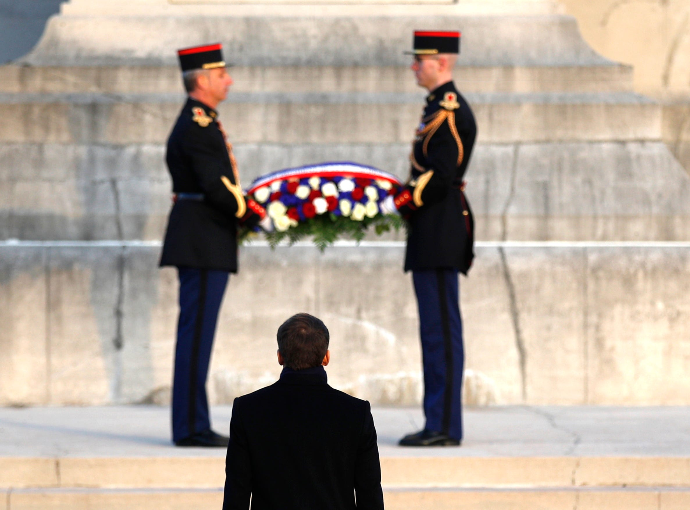 French President Emmanuel Macron is about to lay a wreath of flowers at the monument of the Notre Dame de Lorette war cemetery near Arras, northern France, Thursday, Nov.8, 2018.