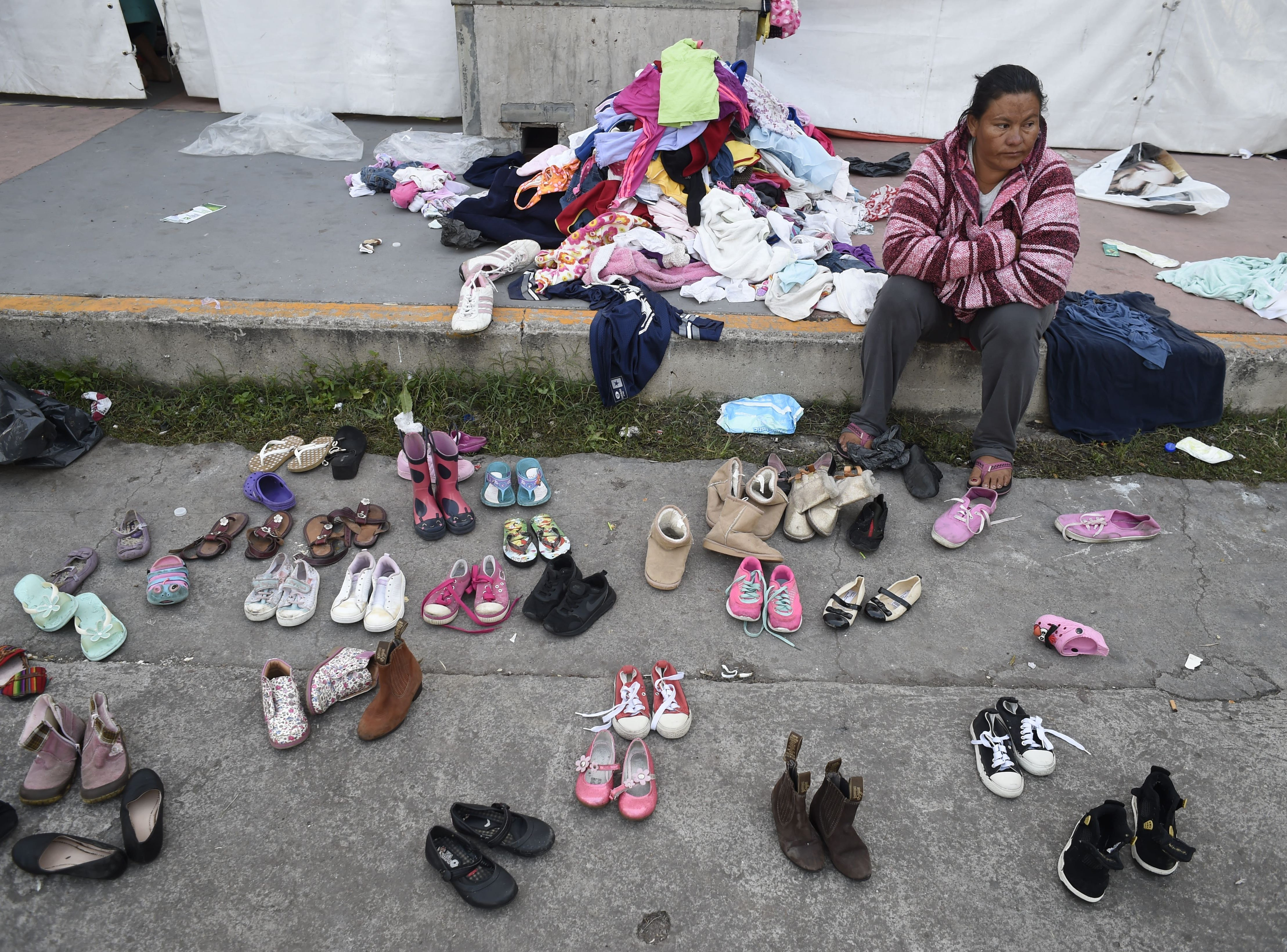 A Central American migrant sits next to donated clothes and shoes during a stopover in Mexico City on Nov. 8, 2018.