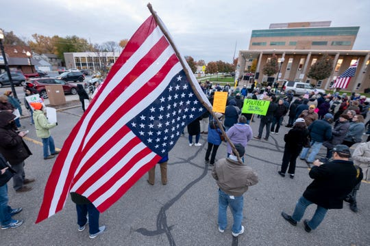 A protestor holds an upside down American flag, a sign of distress, during a protest Thursday evening at Ferndale City Hall to demand that Special Counsel Robert Mueller's investigation be protected in the wake of the firing of U.S. Attorney General Jeff Sessions.  The protest was one of hundreds across the nation.
