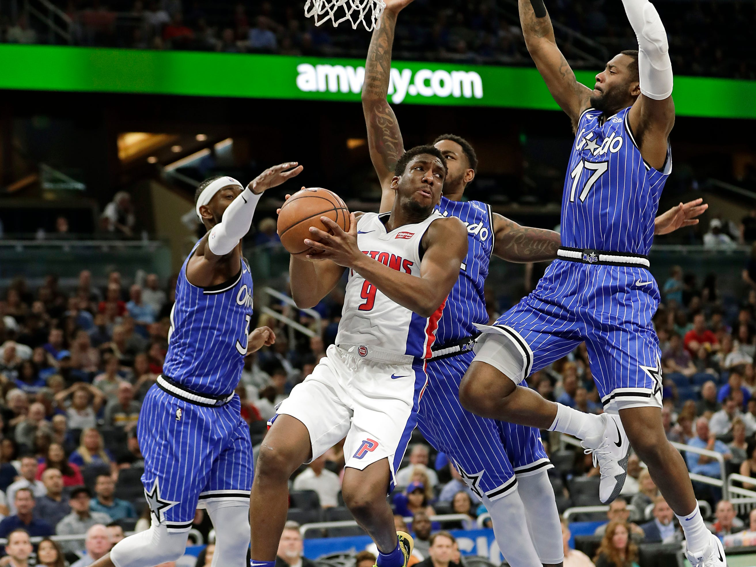 Detroit Pistons' Langston Galloway, center, looks to pass the ball as he is defended by Orlando Magic's Terrence Ross, left, Jarell Martin, second from right, and Jonathon Simmons (17) during the first half of an NBA basketball game, Wednesday, Nov. 7, 2018, in Orlando, Fla.