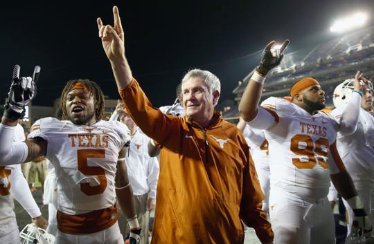 Head coach Mack Brown of the Texas Longhorns celebrates with Desmond Jackson, right, and Josh Turner after beating the TCU Horned Frogs 30-7 in 2013 in Fort Worth, Texas.