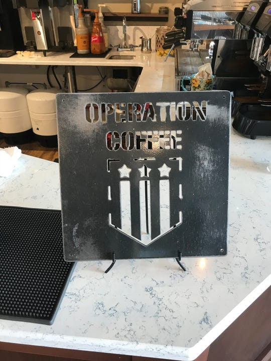 "An ""Operation Coffee"" plaque is on the counter of Blue Door Coffee Co. The plaque was made by a Black Hawk pilot from Seattle, Washington."