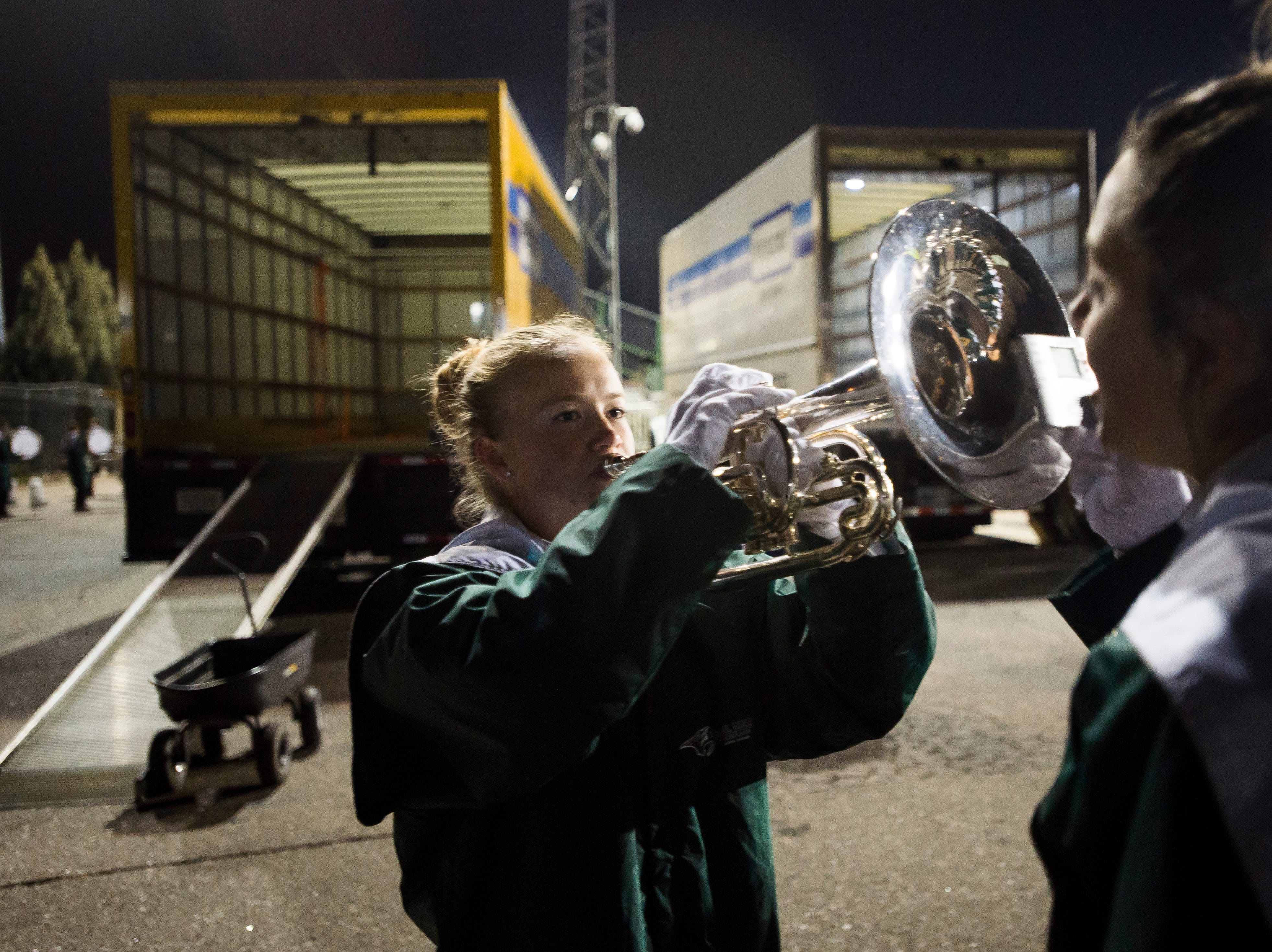 "Fossil Ridge High School marching band member Kailey Diaz, right, helps Calista Johnson tune her mellophone before performing an encore performance of their state-title-winning ""Enlightenment"" on Wednesday, Nov. 7, 2018, at French Field in Fort Collins, Colo."