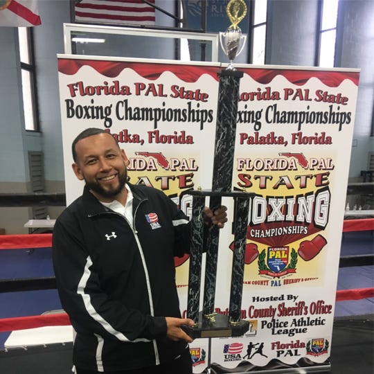 Fort Myers PAL boxing coach Jose Ojeda with Best of Show Team Trophy.