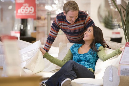 Young Couple Shopping Man Smiling At Woman On Sofa