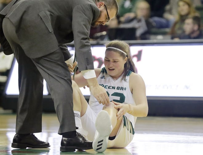 UWGB forward Karly Murphy (32) holds her knee early in the game against Northwestern on Tuesday. The team has announced Murphy will miss the rest of the season with a torn ACL.