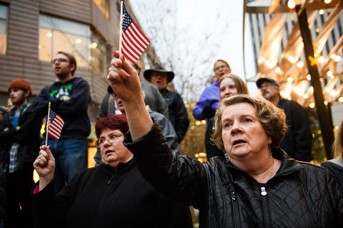 Becky Grose waves an American flag during a protest over fears that President Donald Trump is derailing the Mueller investigation at One City Plaza in downtown Greenville on Thursday, Nov 8, 2018.