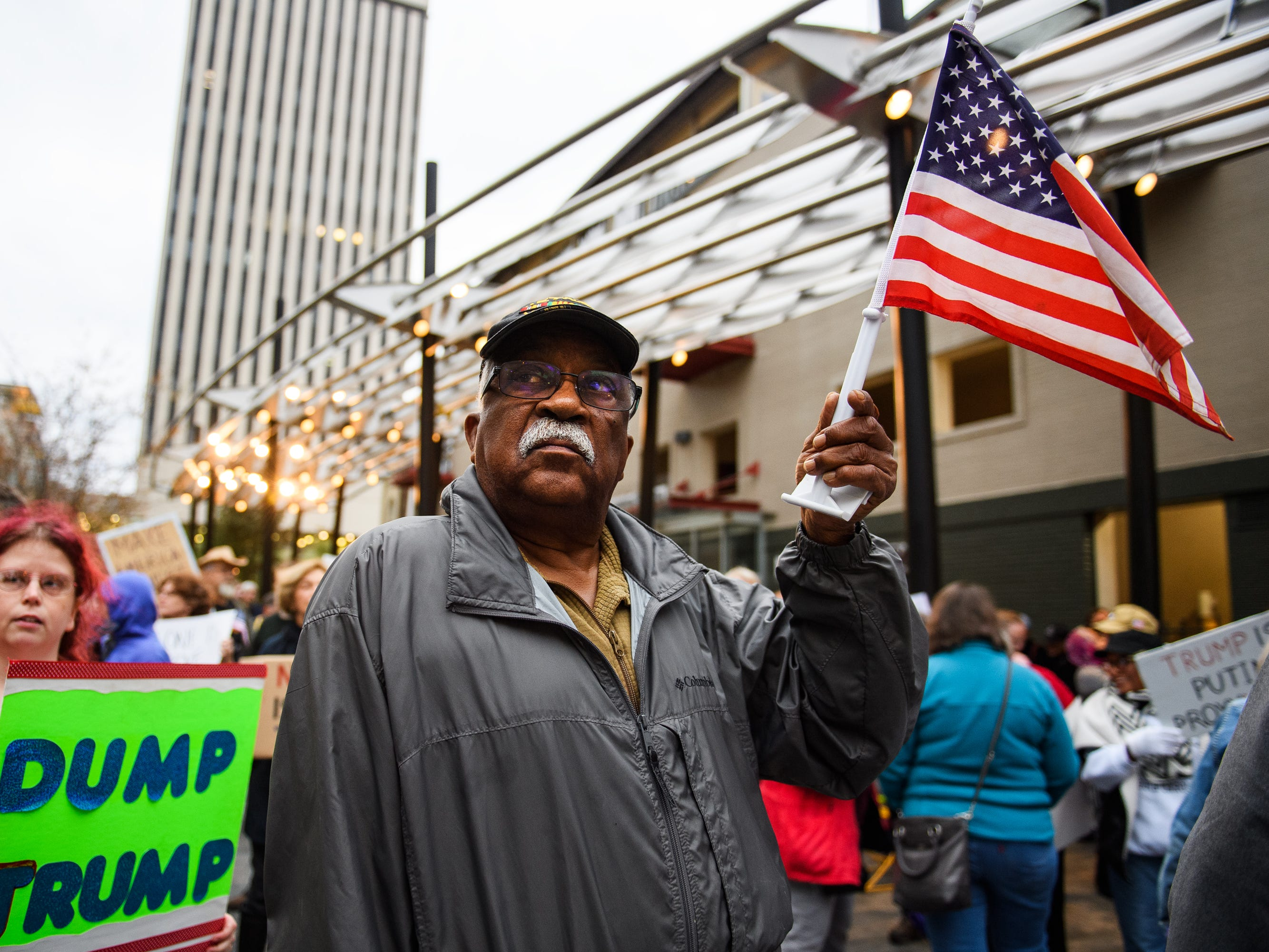 EJ Irick waves an American flag as he and other protesters voice their fears that President Donald Trump is derailing the Mueller investigation at One City Plaza in downtown Greenville on Thursday, Nov 8, 2018.