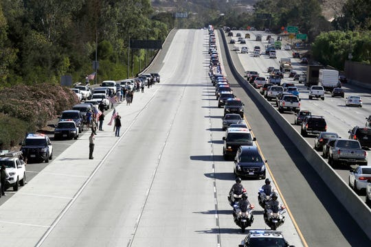 A law enforcement motorcade, providing an escort for a hearse carrying the body of Ventura County Sheriff's Sgt. Ron Helus, makes its way northbound on Highway 101 Thursday, in Newbury Park, Calif. Helus was fatally shot while responding to a mass shooting at a country music bar in Southern California. (AP Photo/Marcio Jose Sanchez)