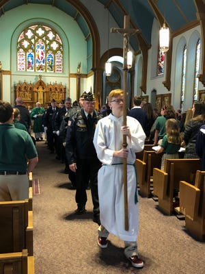 Sam Long leads veterans out of Holy Name of Jesus Catholic Church at the conclusion of Holy Name School's Veterans Day Mass Thursday morning.