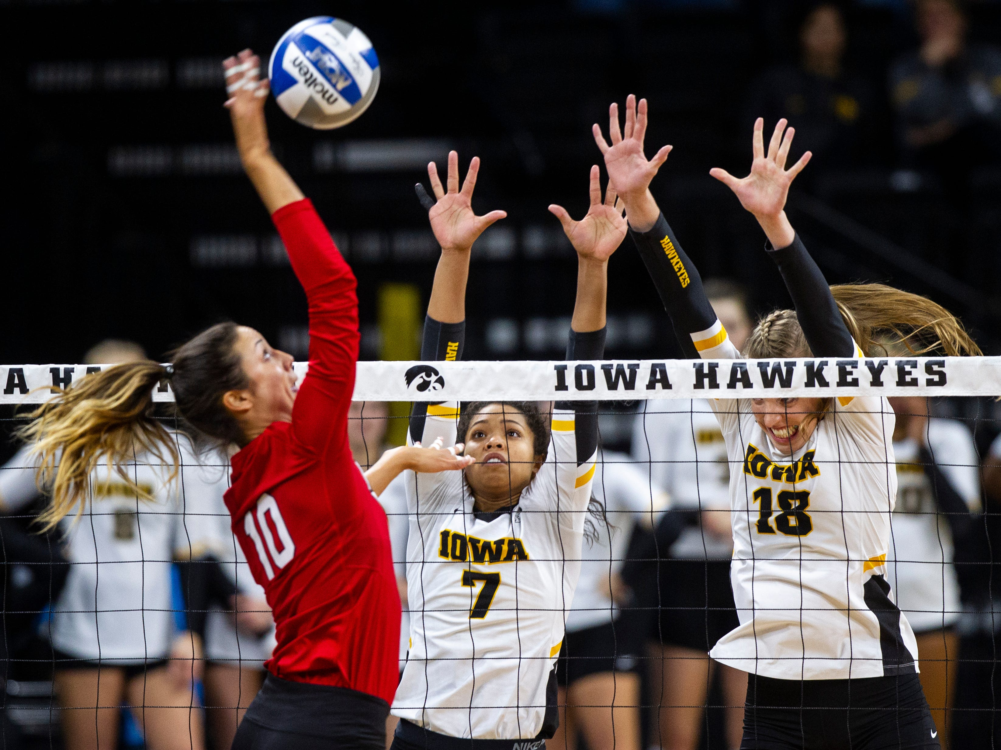 Nebraska's Lexi Sun (10) gets a ball past Iowa setter Brie Orr (7) and middle blocker Hannah Clayton (18) during an NCAA volleyball game on Wednesday, Nov. 7, 2018, at Carver-Hawkeye Arena in Iowa City.