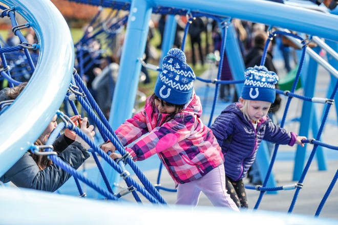 Children and adults play on newly installed equipment  during the grand opening celebration of the Colts Canal Play Space in Indianapolis on Thursday, Nov. 8, 2018.