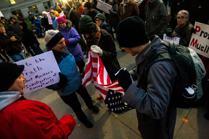 Two people hold an American flag upside down to signal distress during a protest over the appointment of Matt Whitaker as acting U.S. Attorney General on Thursday, Nov. 8, 2018, on east side of the Pentacrest in Iowa City.