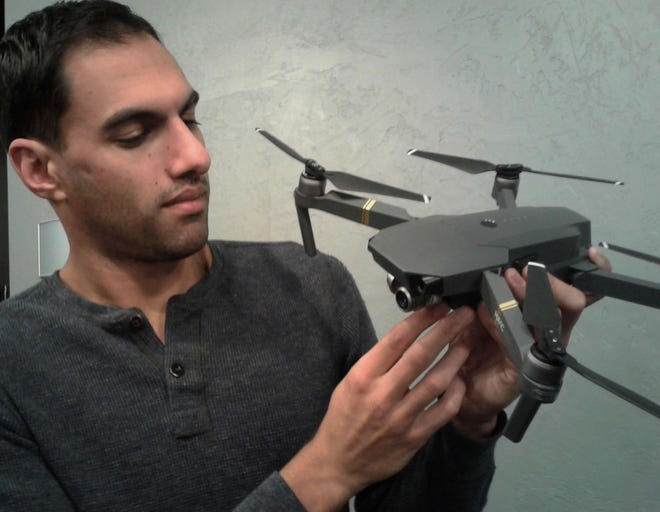 Iowa City native Richard Redfern examines a Mavic Pro drone with camera which he uses for filming everything from car dealership commercials to events at Kinnick Stadium to award-winning documentaries.