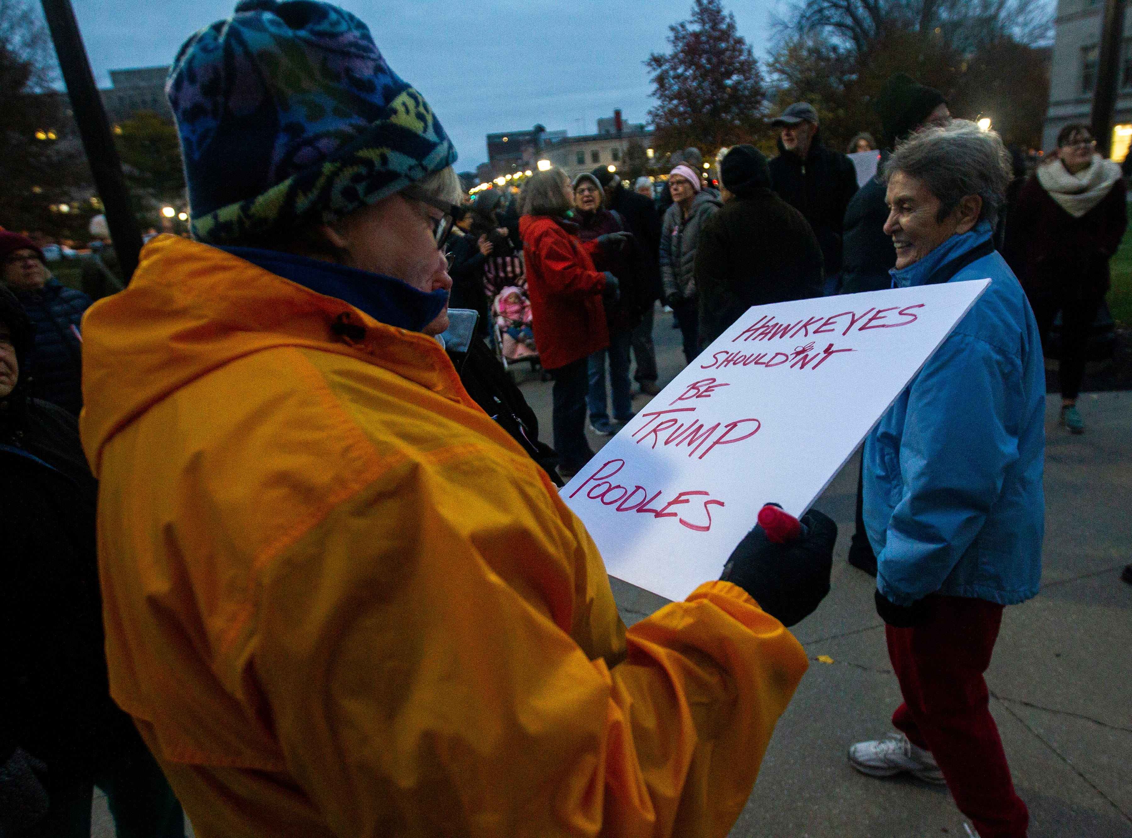 "Jane Langdon, of Temecula, Calif. puts the finishing touches on her sign that reads, ""Hawkeys shouldn't be Trump poodles,"" during a protest over the appointment of Matt Whitaker as acting U.S. Attorney General on Thursday, Nov. 8, 2018, on east side of the Pentacrest in Iowa City. Langdon was in Iowa City visiting a family member and decided to join the protest against the former Iowa Hawkeyes football player, now acting AG."