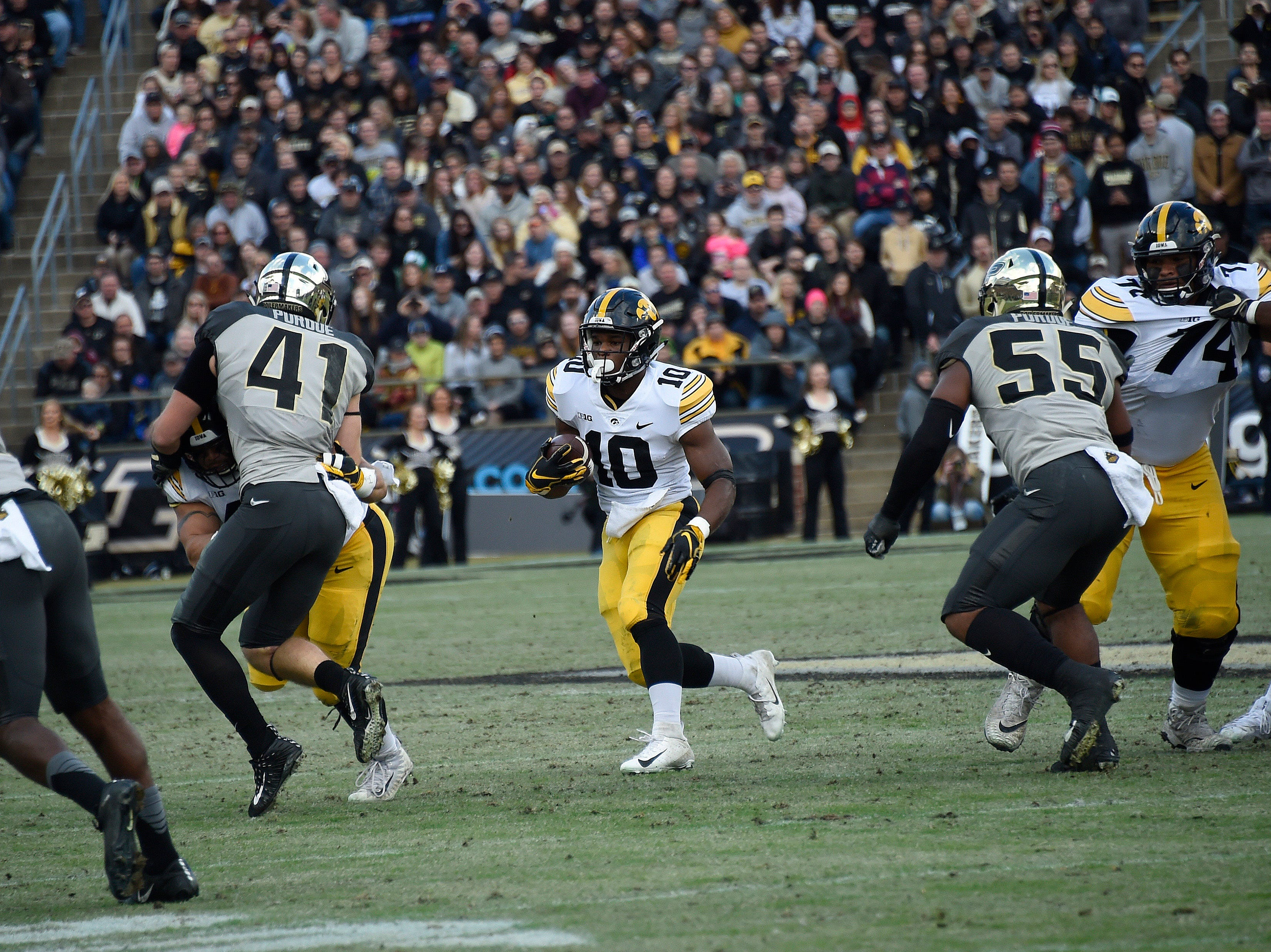 Nov 3, 2018; West Lafayette, IN, USA;  Iowa Hawkeyes running back Mekhi Sargent (10) looks for room to run between defenders Purdue Boilermakers safety Jacob Thieneman (41) and linebacker Derrick Barnes (55) at Ross-Ade Stadium.