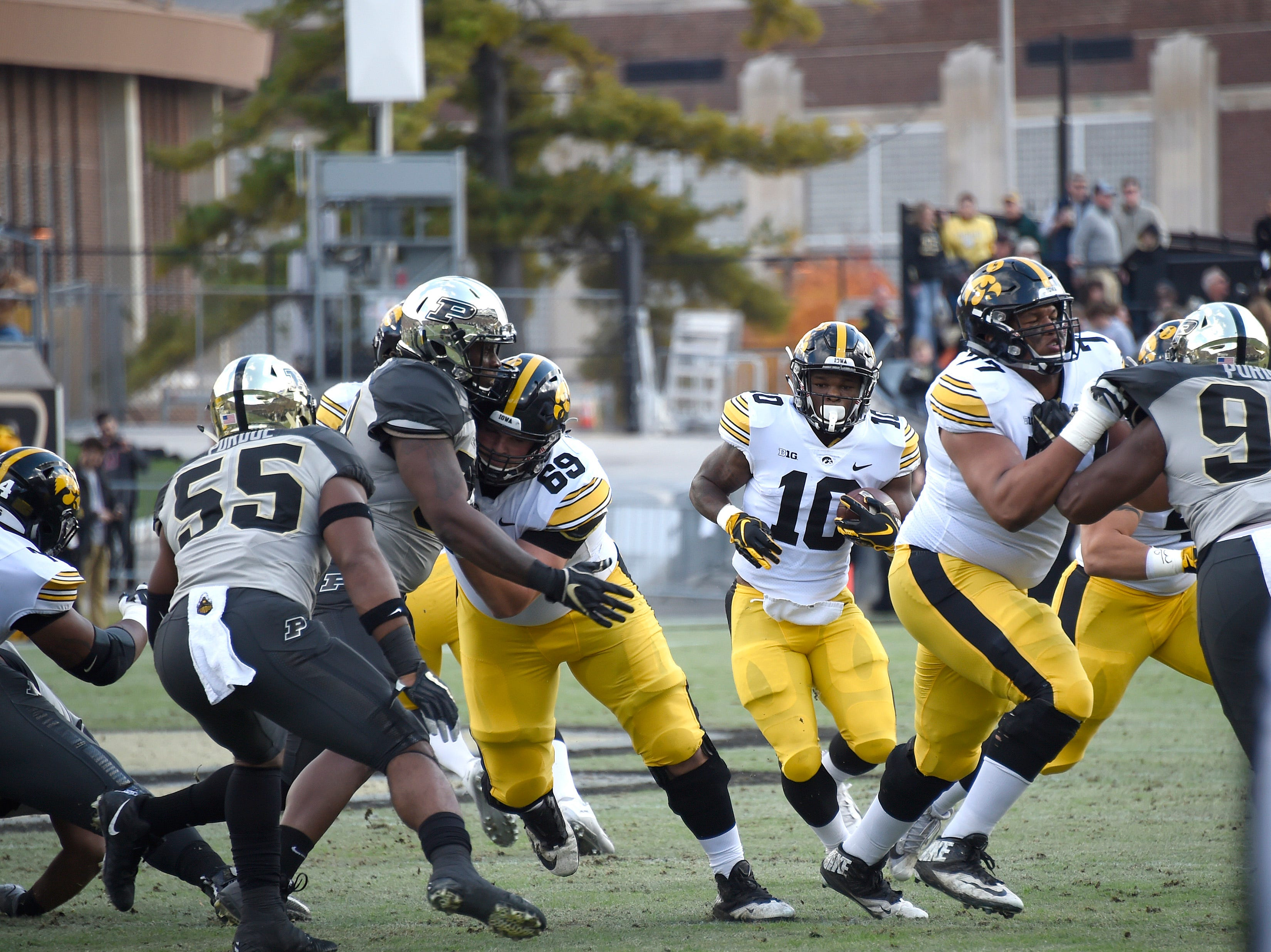Nov 3, 2018; West Lafayette, IN, USA;  Iowa Hawkeyes running back Mekhi Sargent (10) looks for room to run behind his blockers lineman Keegan Render (69) and  Alaric Jackson (77) against the Purdue Boilermakers at Ross-Ade Stadium.