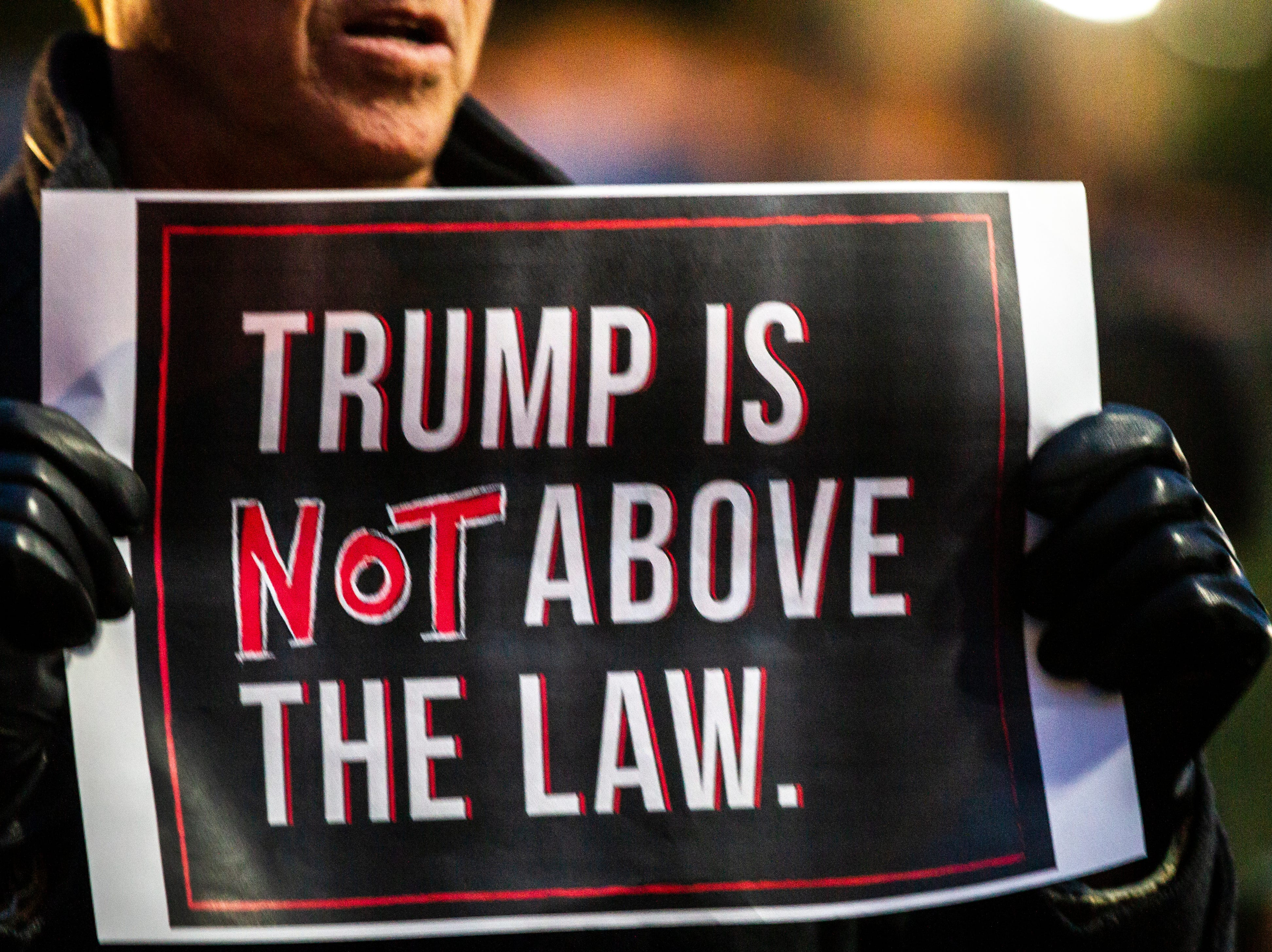 "A man holds a sign reading ""Trump is not above the law."" during a protest over the appointment of Matt Whitaker as acting U.S. Attorney General on Thursday, Nov. 8, 2018, on east side of the Pentacrest in Iowa City."