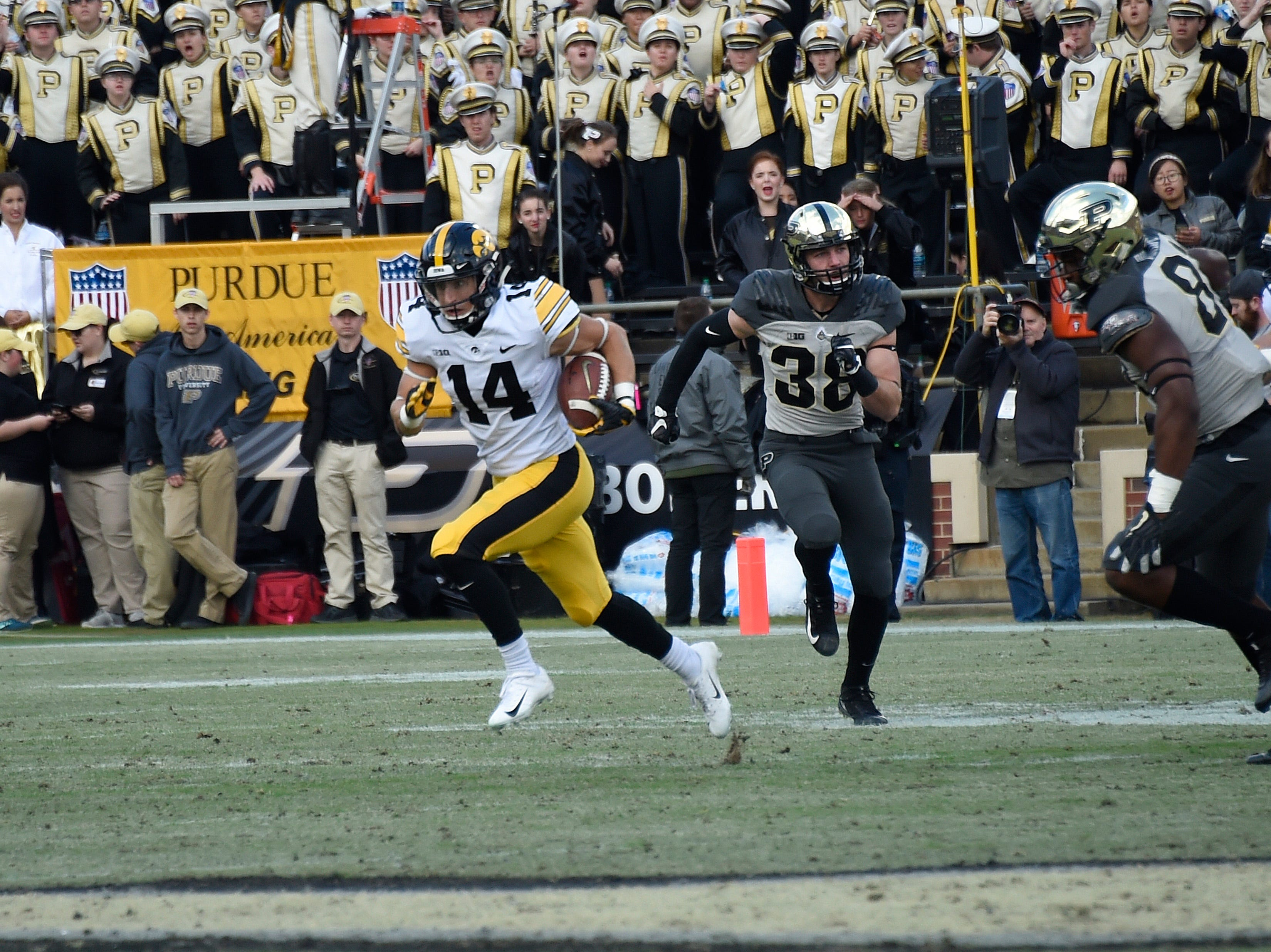 Nov 3, 2018; West Lafayette, IN, USA;  Iowa Hawkeyes wide receiver Kyle Groeneweg (14) runs with the ball as  Purdue Boilermakers safety Brennan Thieneman (38) pursues him at Ross-Ade Stadium.