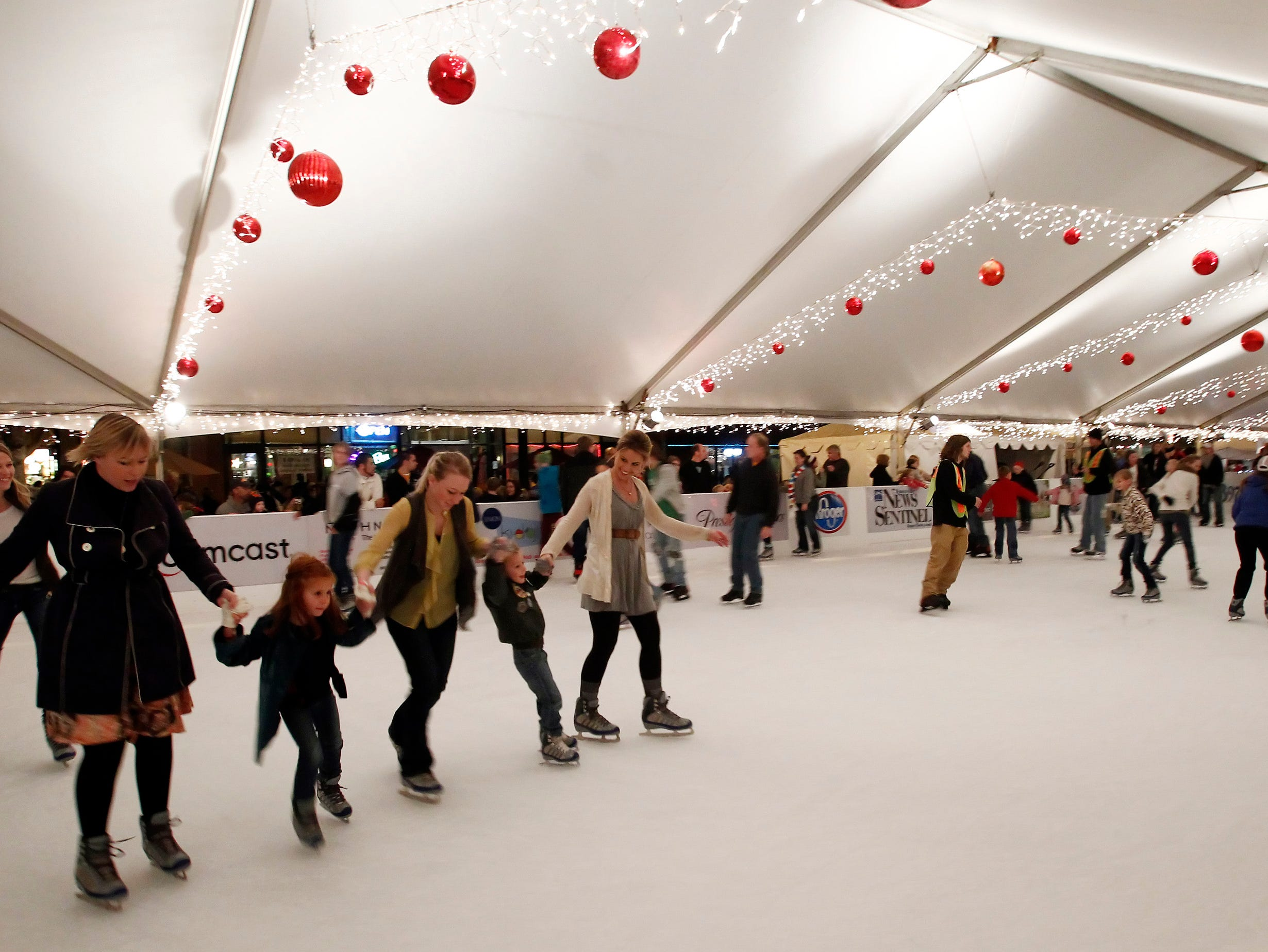 People ice skate on Market Square during Christmas festivities Friday, Nov. 25, 2011.