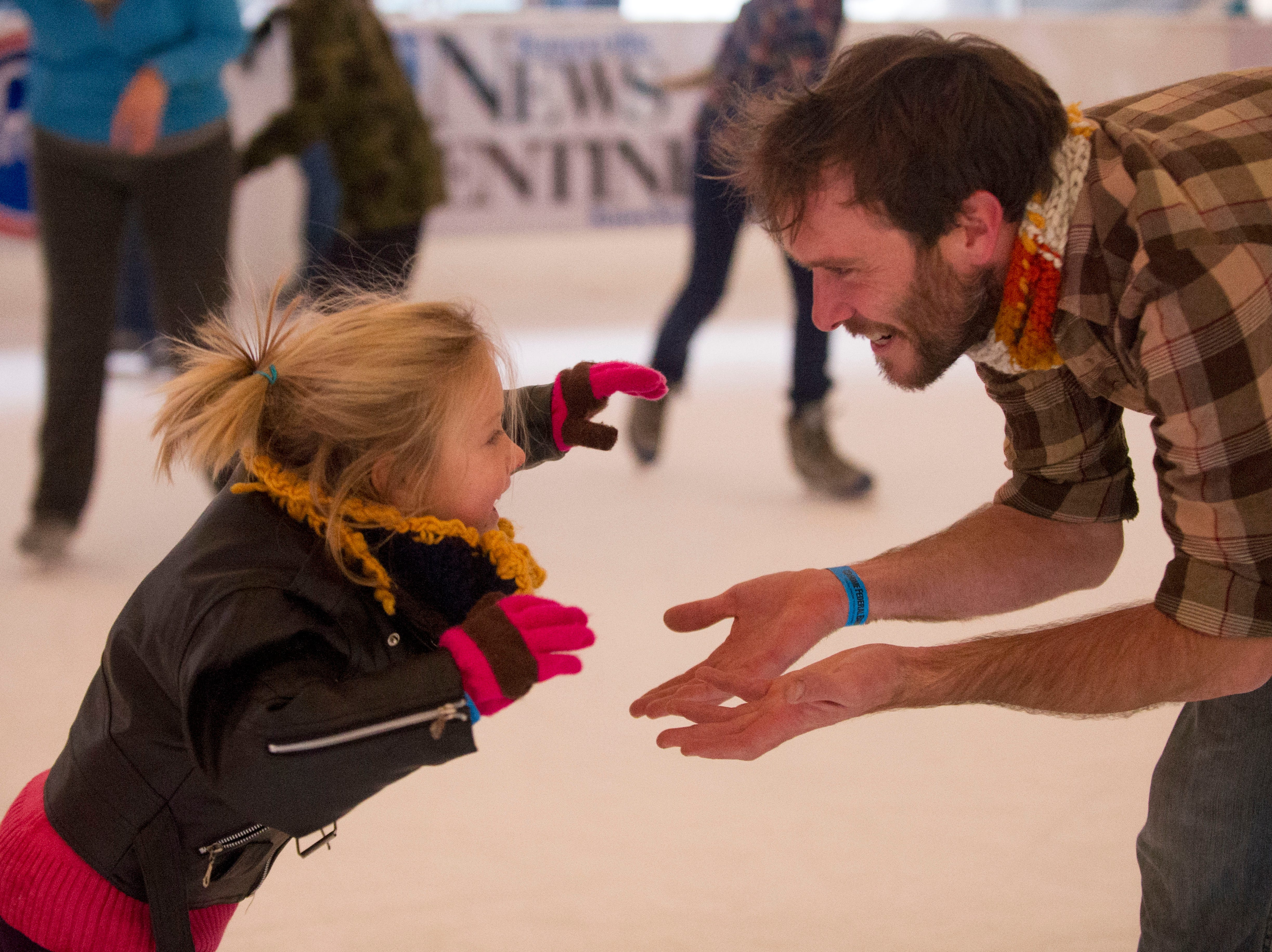 "Violet Epperson-Scott, 5, reaches out to her father Ben Epperson while she learns how to skate at Knoxville's Holidays on Ice on Sunday, December 23, 2012. ""We've specifically came out to ice skate."" Says Epperson of his two daughters. ""This is their first time. They did really well. We fell a little bit."" So far, more than 10,000 people have skated at the ice rink according Holiday on Ice manager Robyn Wilson. ""We're very hopeful that we may have more than 20,000 skaters this year."" She adds."