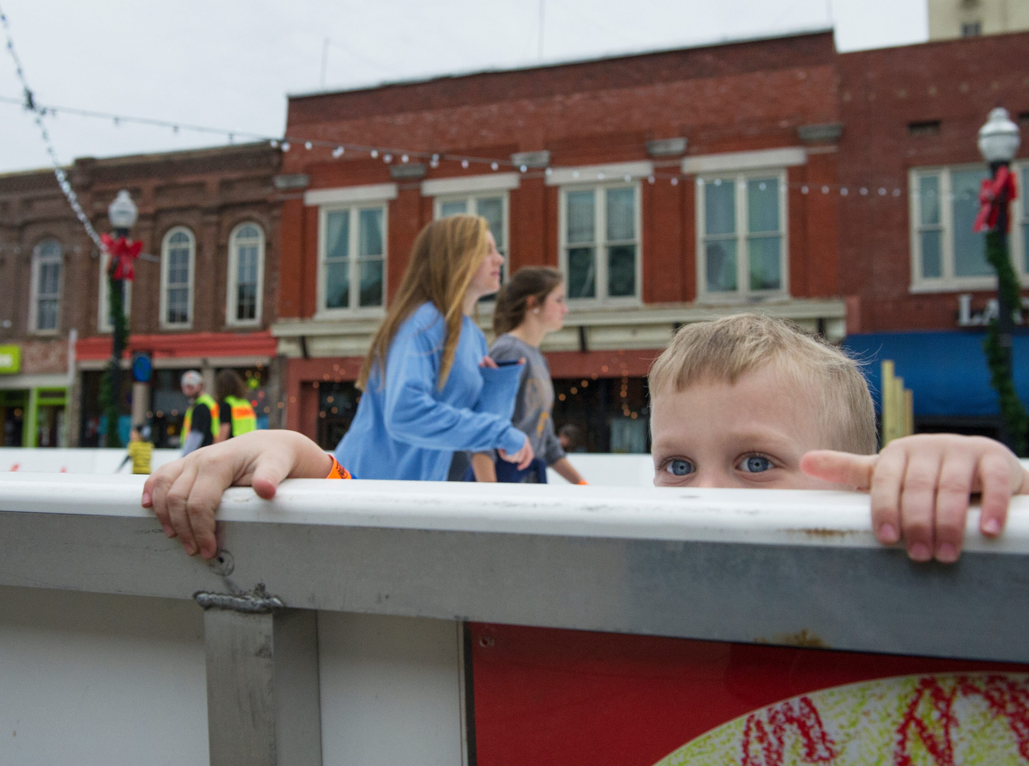 Keaton Smith, 5, of Florida holds onto the wall to keep his balance during the opening weekend for the Market Square ice skating rink Saturday, Nov. 28, 2015.