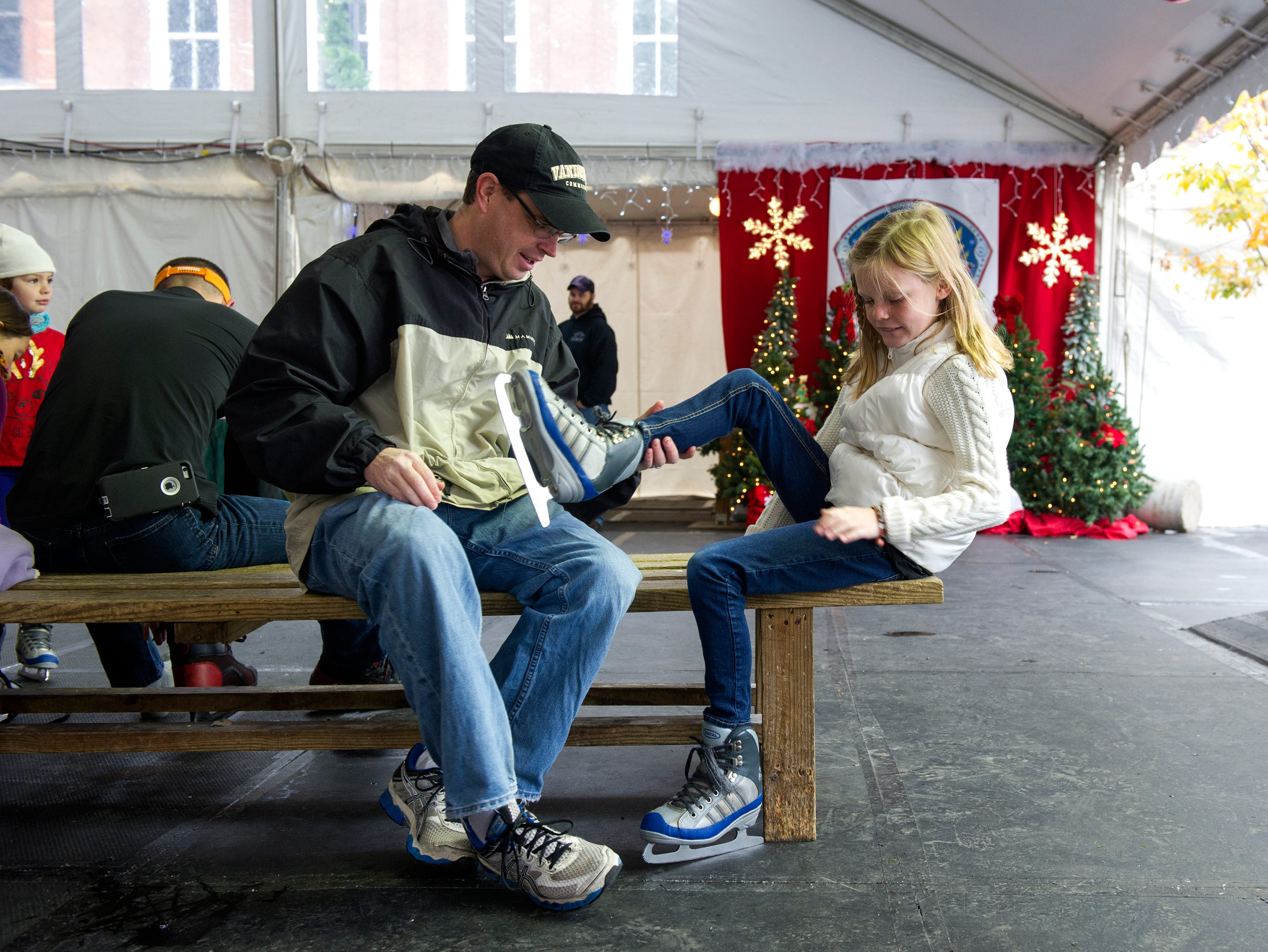 Marshall Bartlett (left) helps his daughter Erin Bartlett, 9, get her skates on during opening weekend for the Market Square ice skating rink Saturday, Nov. 28, 2015.