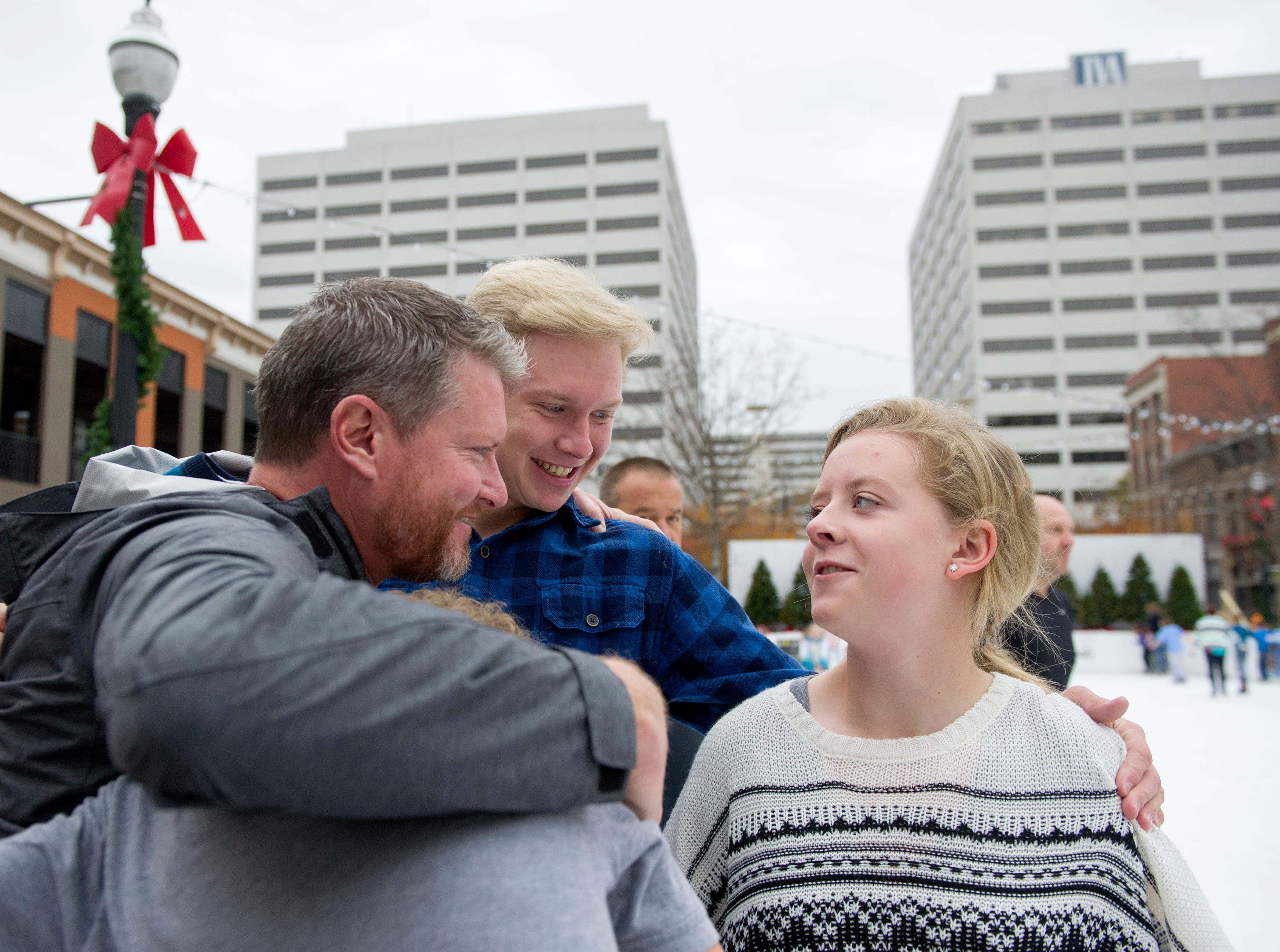 Eric Rice (left) pulls his kids Jake Rice, Emma Rice (right) and Charlie Rice all of Knoxville in for a hug during opening weekend for the Market Square ice skating rink Saturday, Nov. 28, 2015.