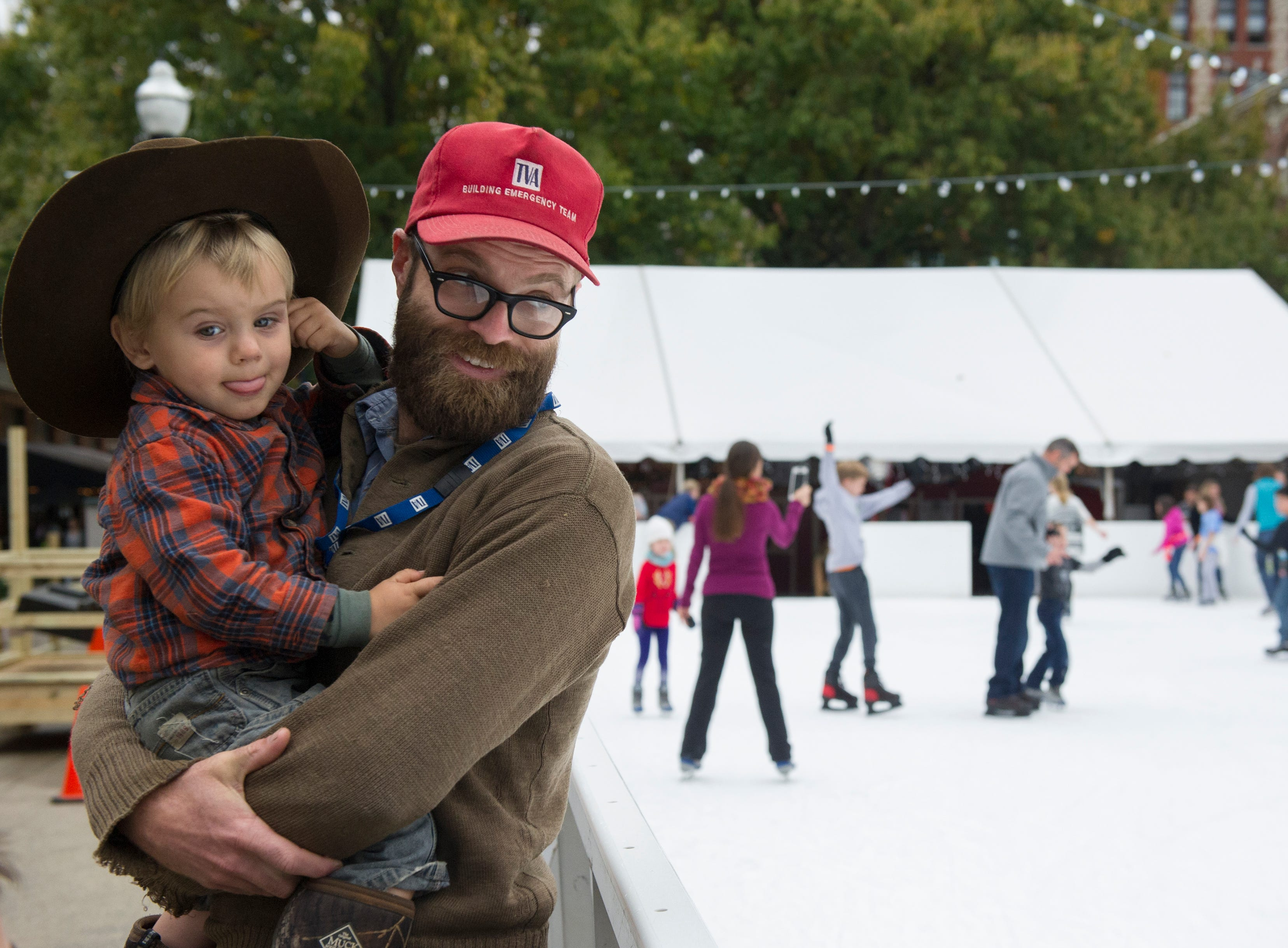 William Cantrell of Knoxville (right) holds his son Woodrow Cantrell, 2, as they watch skaters during opening weekend for the Market Square ice skating rink Saturday, Nov. 28, 2015.