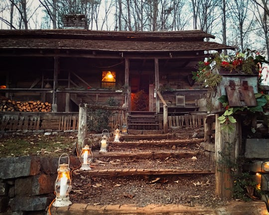 Log cabins are decorated for the Museum of Appalachia's evening Candlelight Christmas events.