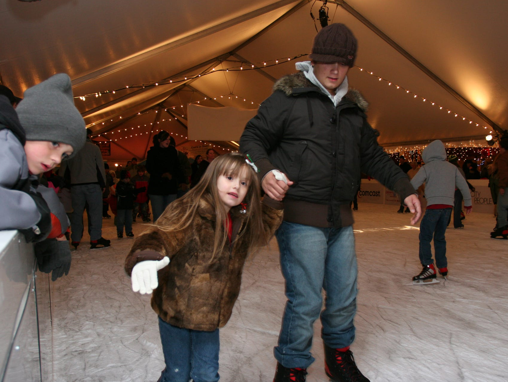 Amber Baker, 6, ice skates with her brother Jason Higgs, 15, during the kick off for Christmas in the City on Friday in Market Square. Tyler Pearcy, 7, watches the action at left.