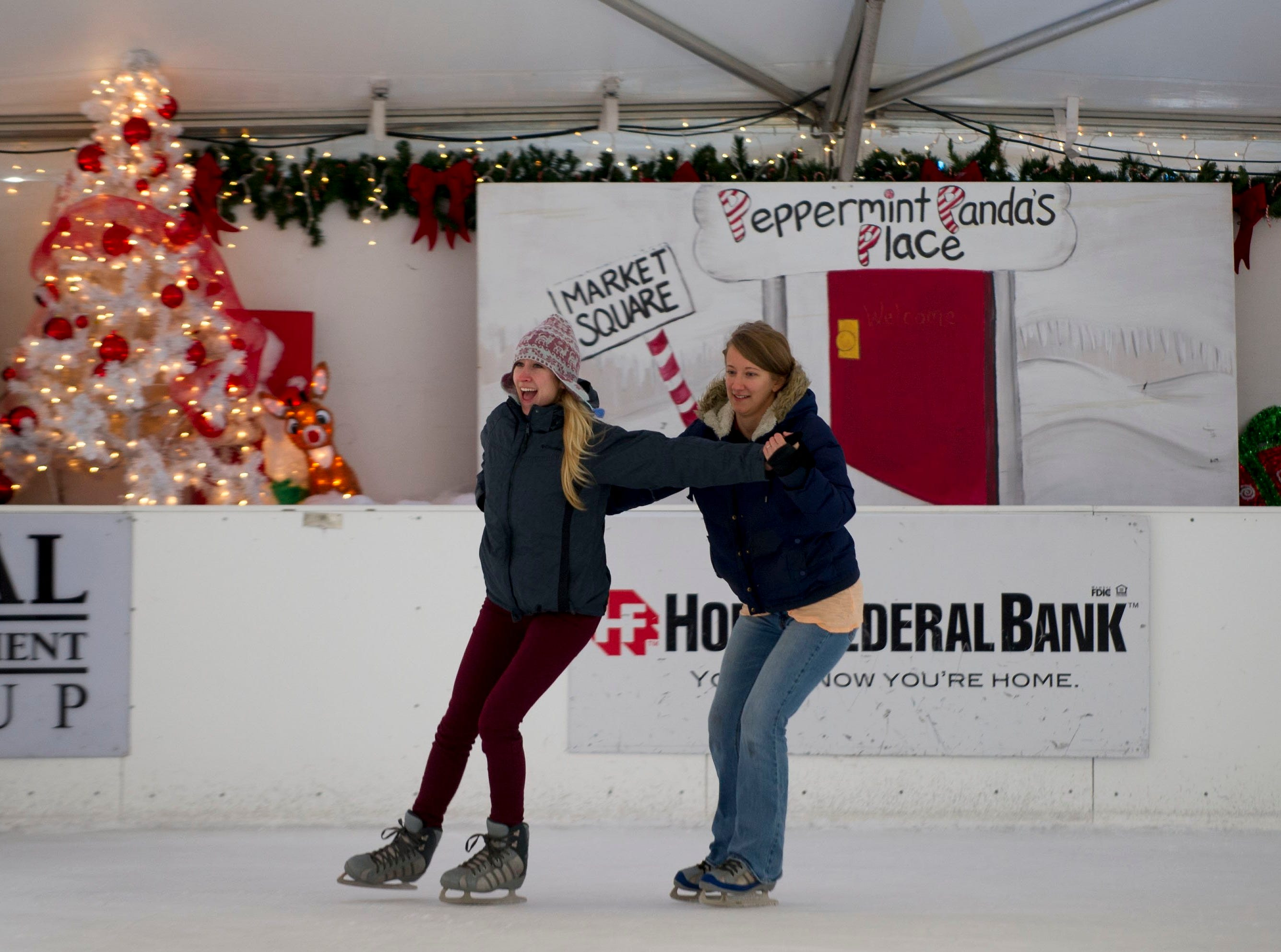Sisters Erica Sladky, left and Tegan Sladky, right show off their skating skill at the outdoor ice skating rink on Market Square in downtown Knoxville Tuesday December 24, 2013.