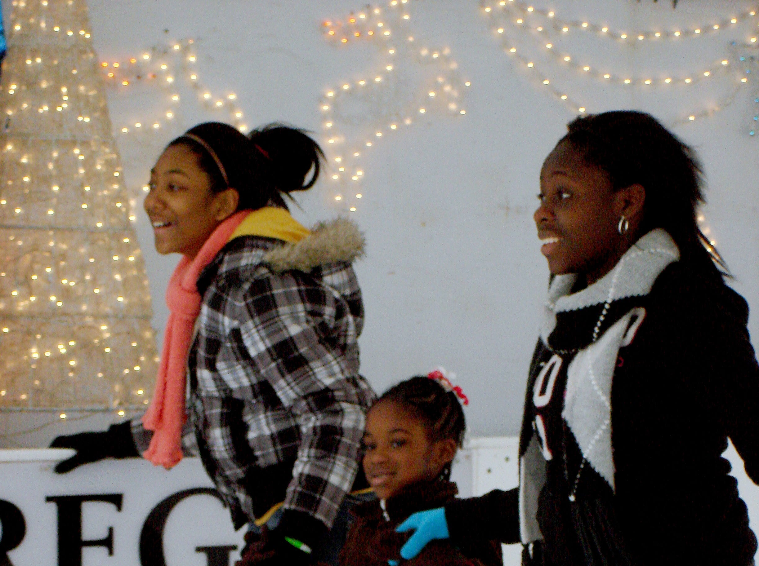 From left, Talayia Kelly, Zi Nzie and Marissa Sexton, members of the Boys & Girls Club, have fun while ice skating on Market Square.
