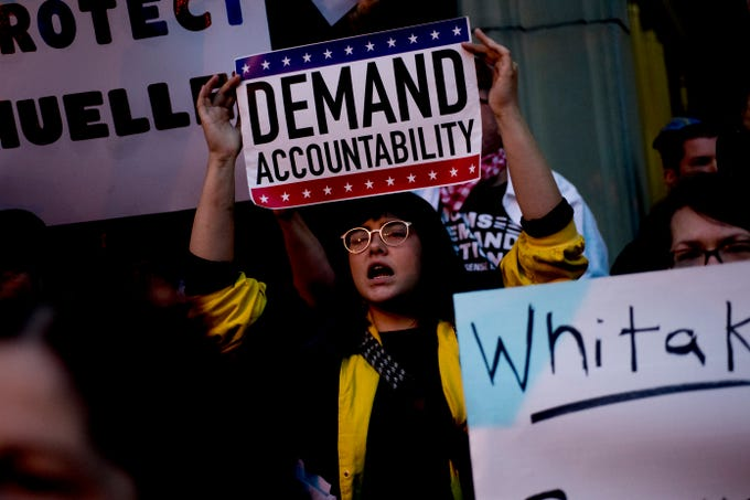 "A protester chants while holding a sign reading ""Demand Accountability"" during a protest against the firing of United States Attorney General Jeff Sessions outside of the Federal Courthouse in Knoxville, Tennessee on Thursday, November 8, 2018."