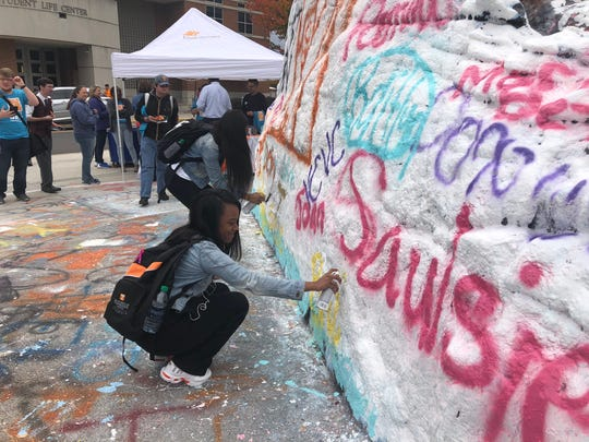 Brakala Sims, a freshman first-generation student at the University of Tennessee, Knoxville, paints her name on the Rock as part of National First-Generation College Student Day.