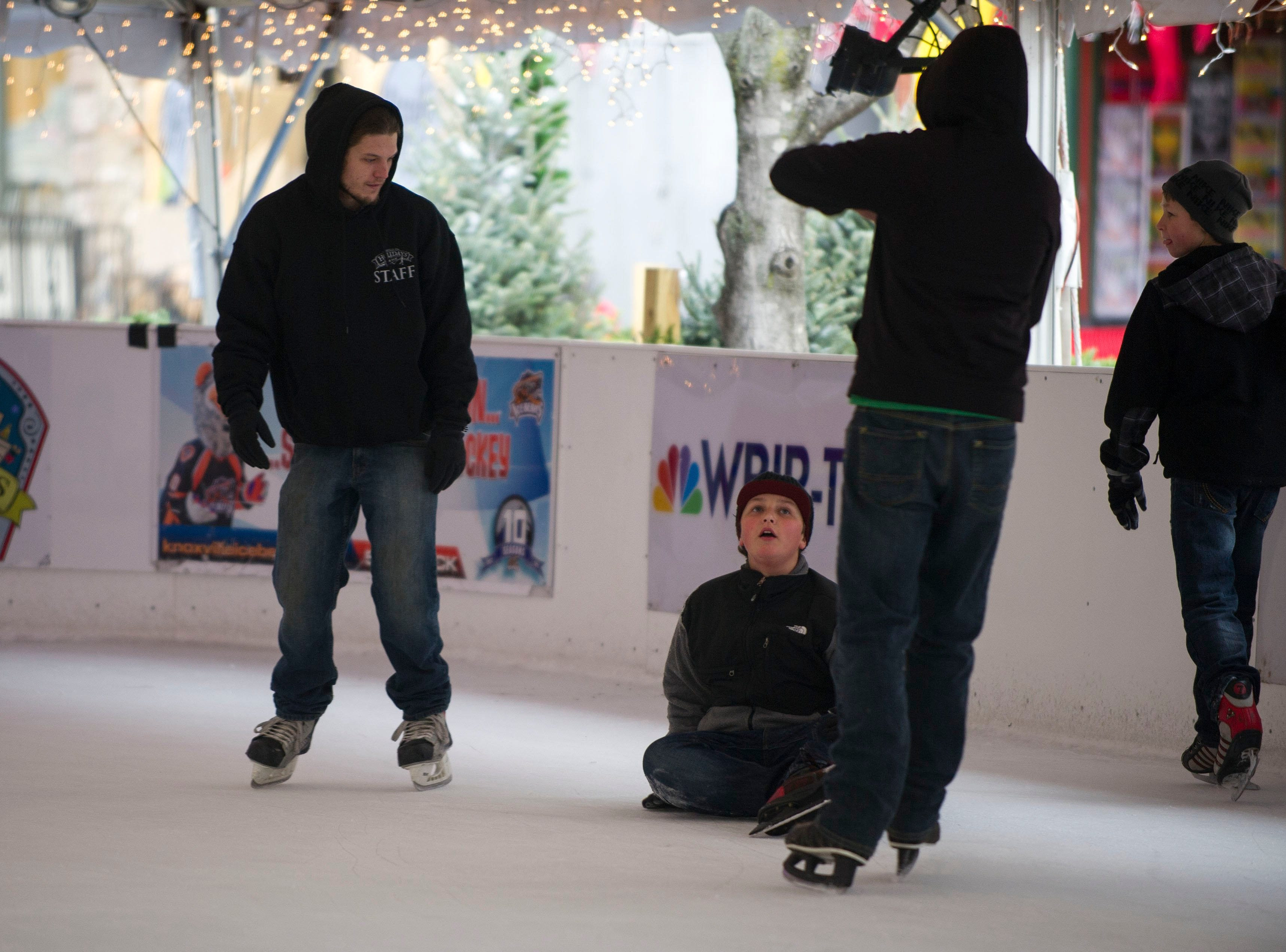 Zach Qualls looks up from the ice as his friends skate by at the outdoor ice skating rink on Market Square in downtown Knoxville Tuesday December 24, 2013.