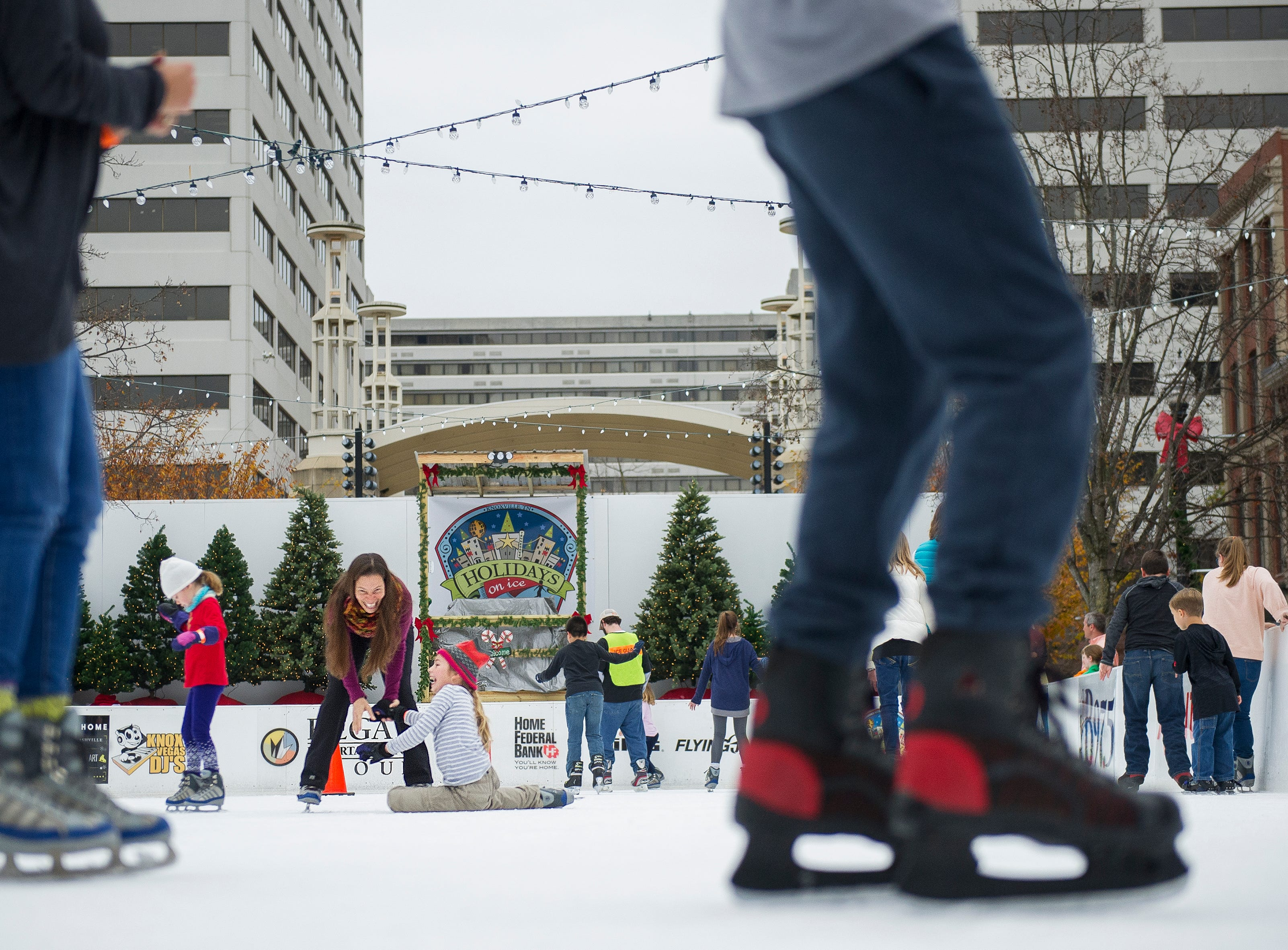 Gina Brace (center) laughs has she helps her daughter Gigi Brace, 9, up after she fell during opening weekend for the Market Square ice skating rink Saturday, Nov. 28, 2015.