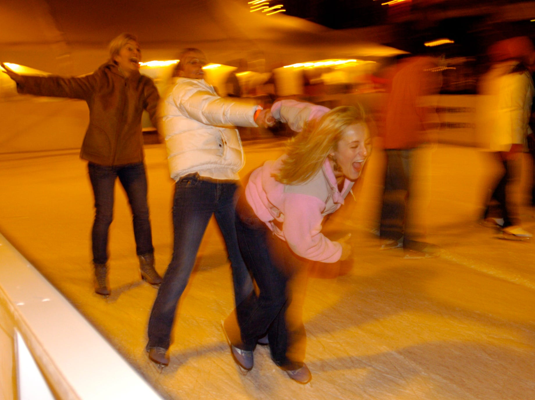 "Sarah Brann, right, leads her roommates Haley Dickson, center, and Gertrude Eggers around the ice at the ""Holidays on Ice"" rink at Market Square. Ice-skating has returned after a 14-year absence as part of Knoxville' s ""Christmas in the City."" 2005"