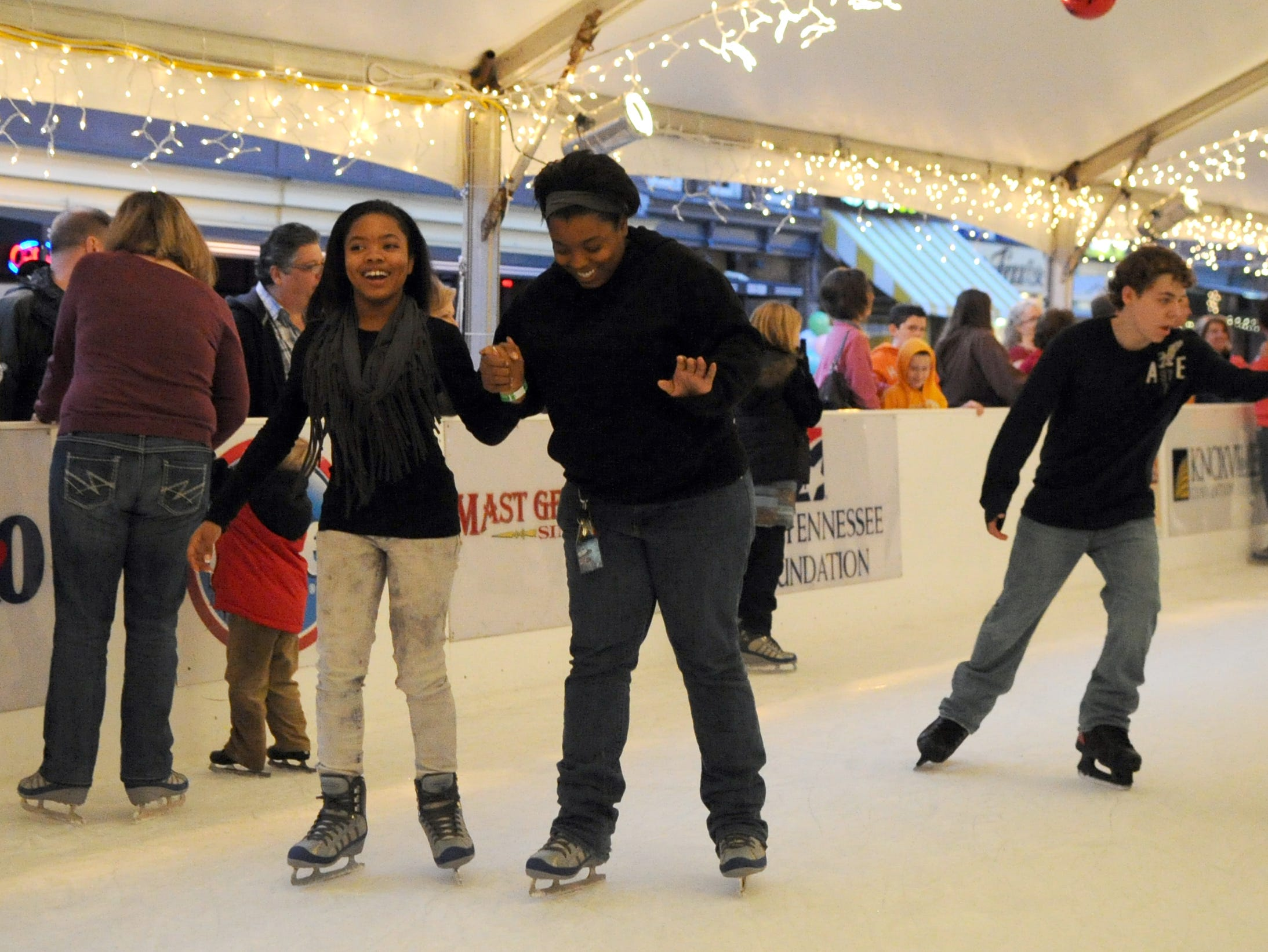 Jada and Courtney Mostella, left to right, skate at the Knoxville's Holidays ice skating rink on Market Square Saturday, Nov. 26, 2011.