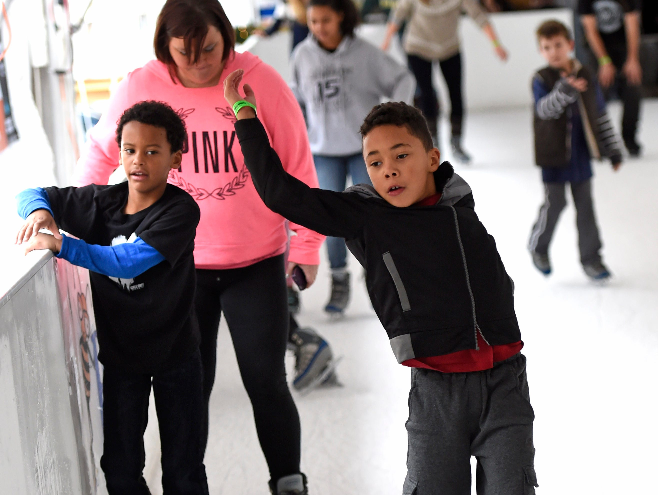Malachi Kirk, center, wobbles as he ice skates for the first time in Market Square on Christmas Eve, Wednesday, Dec. 24, 2014.